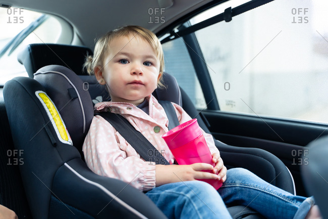 Girl sitting in safety seat with belt fastened and drinking water from plastic cup during trip