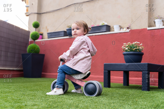 Full length side view of cute toddler girl riding toy bicycle on green lawn near house while spending summer day in yard