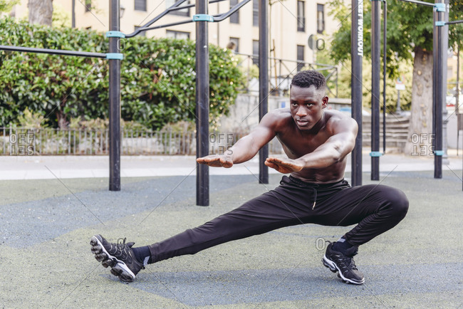 Full body focused shirtless African American athletic male doing side lunges with outstretched arms while training on sports ground