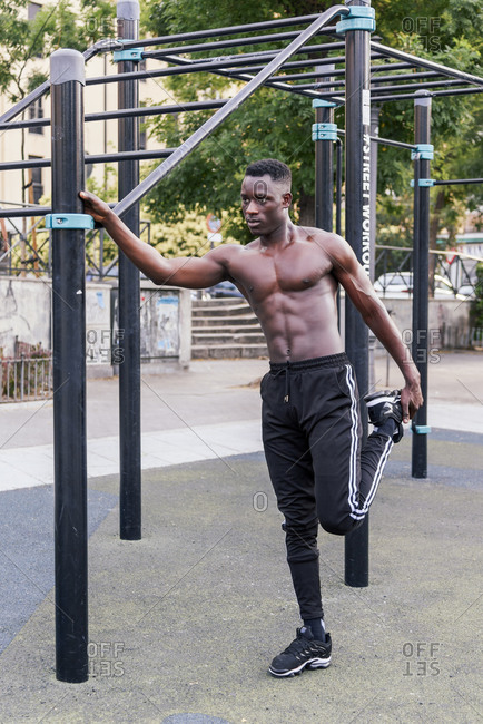 Focused black male athlete with naked torso warming up legs during workout on modern sports ground and looking away