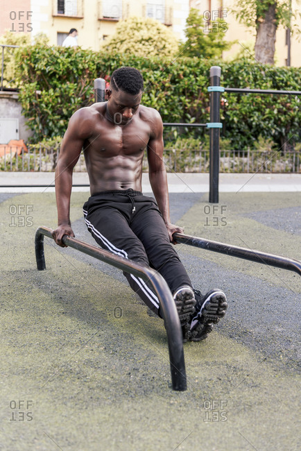 Determined black sportsman doing parallel bar dips on parallel bars during workout on sports ground