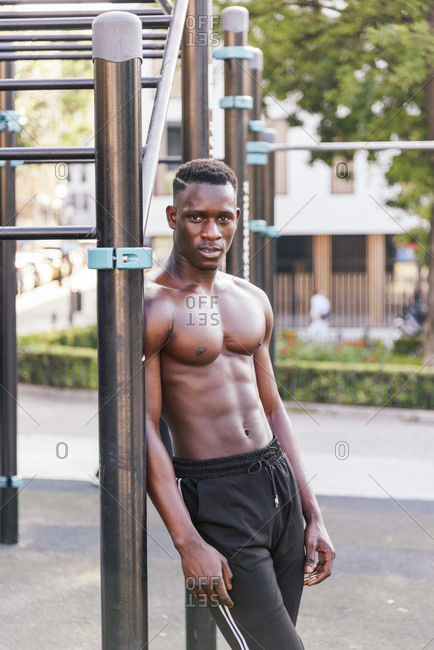 African American sportsman with muscular body standing near metal bars on sports ground and relaxing during training while looking at camera