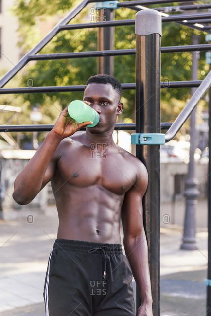 Tired African American male athlete with muscular torso standing on sports ground while enjoying fresh water from bottle and looking away