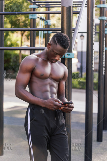Shirtless African American sportsman leaning on metal bars on sports ground and chatting on social media via cellphone after workout while looking down