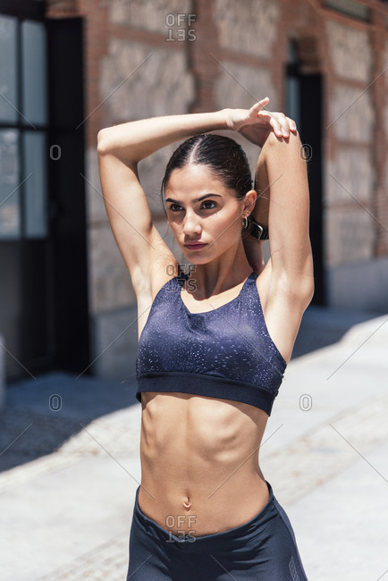 Confident female runner in sports bra and leggings standing on sidewalk and stretching arms while warming up before workout and looking away