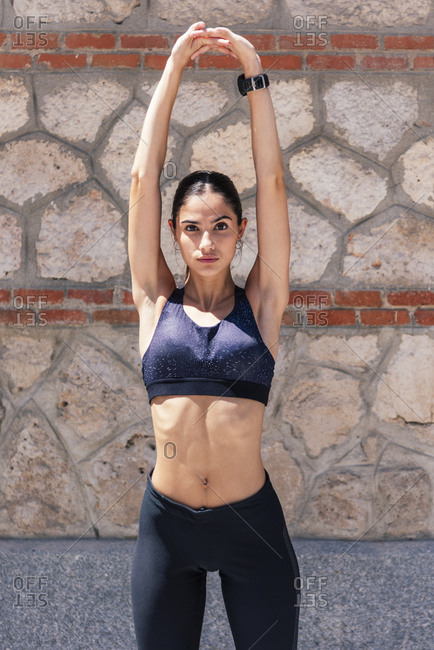 Confident female runner in sports bra and leggings standing on sidewalk and stretching arms while warming up before workout and looking at camera