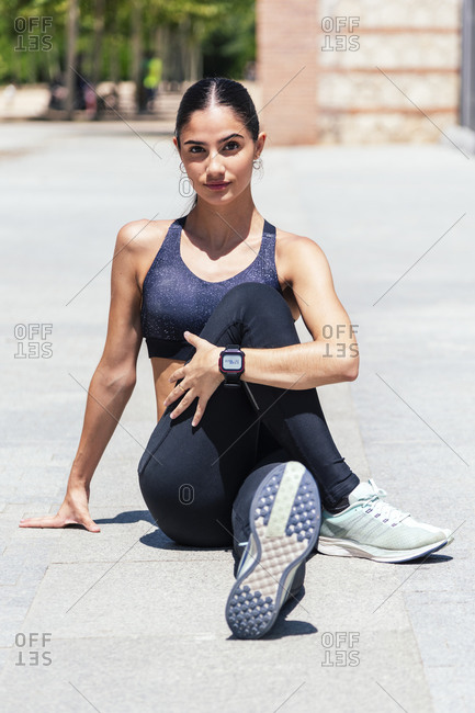 Flexible female athlete in sportswear sitting on pavement and stretching legs before training in city