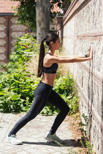 Side view of sportswoman in leggings and bra stretching legs and warming up during workout on sunny day