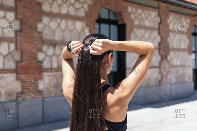 Back view of unrecognizable female in sports bra standing on street and making ponytail before workout