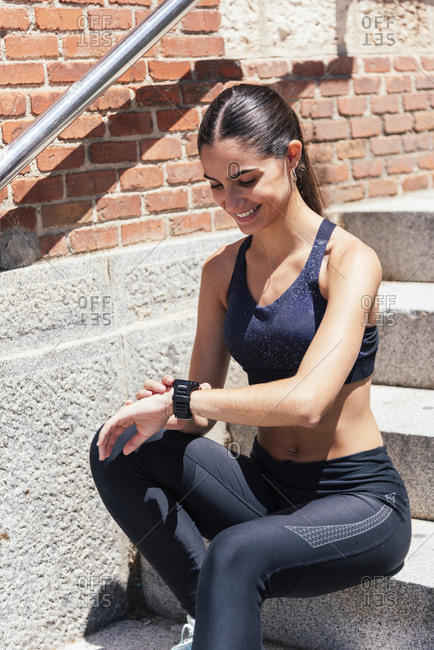 Content female runner sitting on stone stairs in city and measuring pulse on fitness tracker during training on sunny day