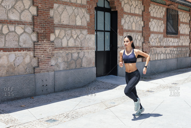 Side view of fit female in sportswear running fast along pavement during training on sunny day in city