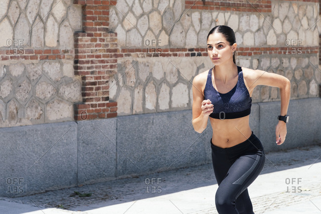 Fit female in sportswear running fast along pavement during training on sunny day in city
