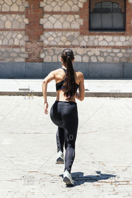 Back view of fit female in sportswear running fast along pavement during training on sunny day in city