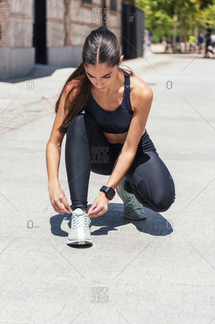 Confident slim female in activewear tying shoelaces on sneakers during training on sunny day in city
