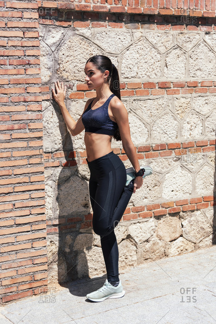 Female athlete in leggings standing near brick wall on street and warming up legs during workout