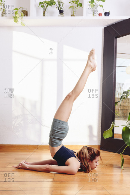 Side view of slim female in Full Locust pose practicing yoga on wooden floor in cozy living room