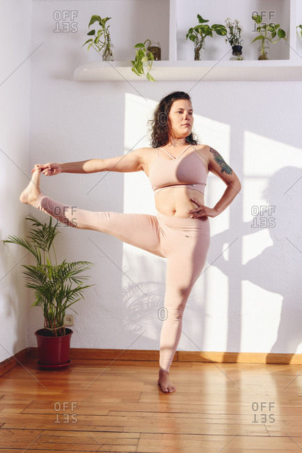 Female in sportswear standing in Hasta Padangusthasana with raised leg and looking at camera while practicing yoga at home
