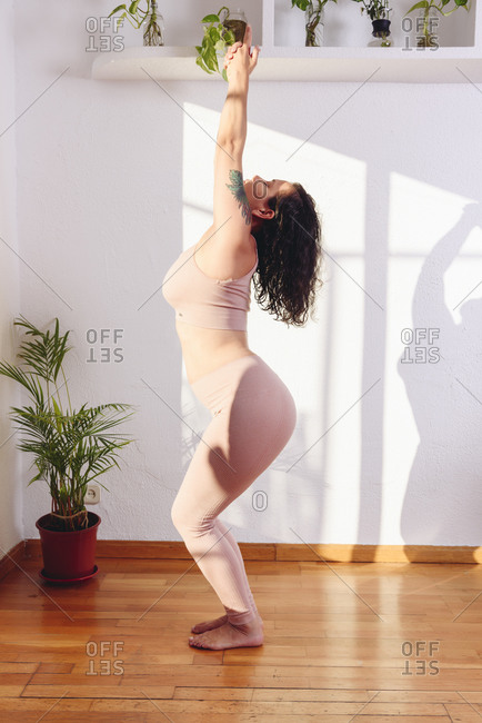 Side view of flexible female in sportswear doing Mountain poses during yoga practice in modern living room