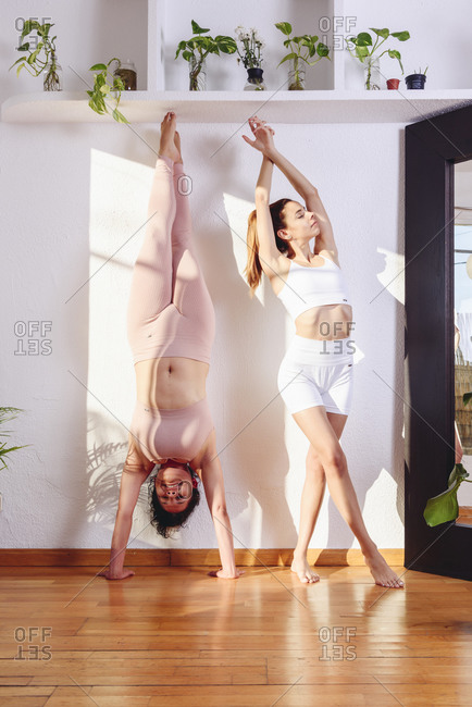 Flexible females in sportswear in Handstand and Mountain poses doing yoga in modern living room