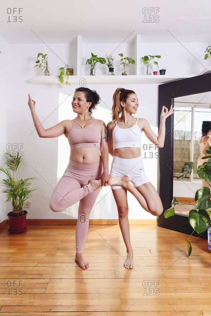 Content female friends standing in Ardha Padmasana with mudra gesture and practicing yoga together in bright living room