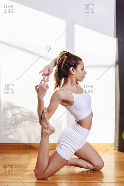 Side view of relaxed female in sportswear practicing yoga in Eka Pada Rajakapotasana while sitting on wooden floor at home