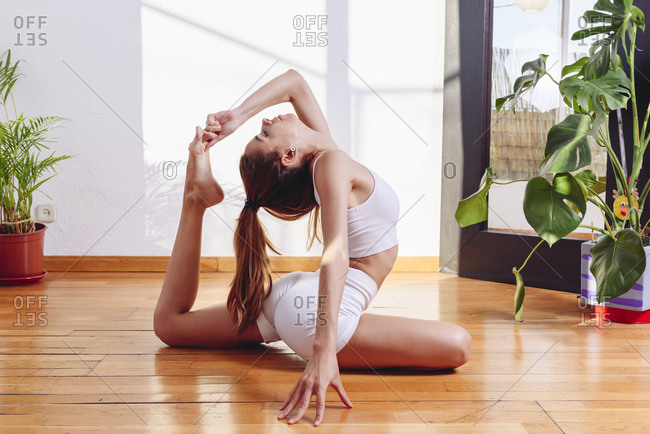 Side view of barefoot female sitting on wooden floor in Eka Pada Rajakapotasana and stretching body while practicing yoga in cozy living room