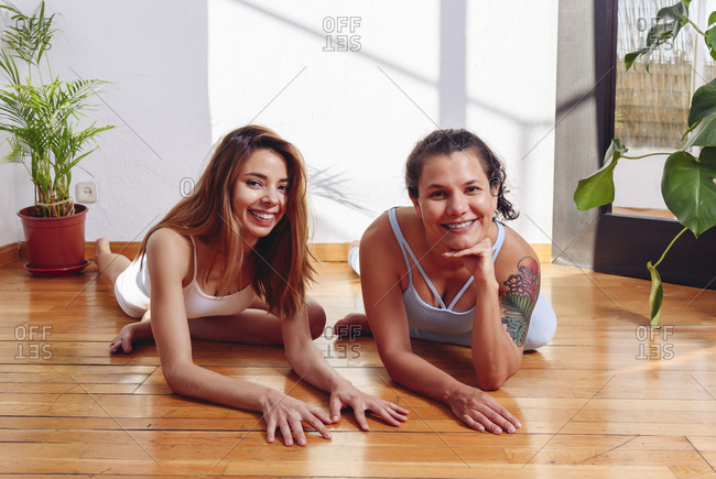 Smiling flexible females in sportswear sitting on floor in Ardha Kapotasana while practicing yoga together at home and looking at camera