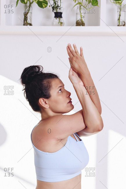 Side view of calm female standing in Utkata Konasana with twisted arms and meditating while practicing yoga at home