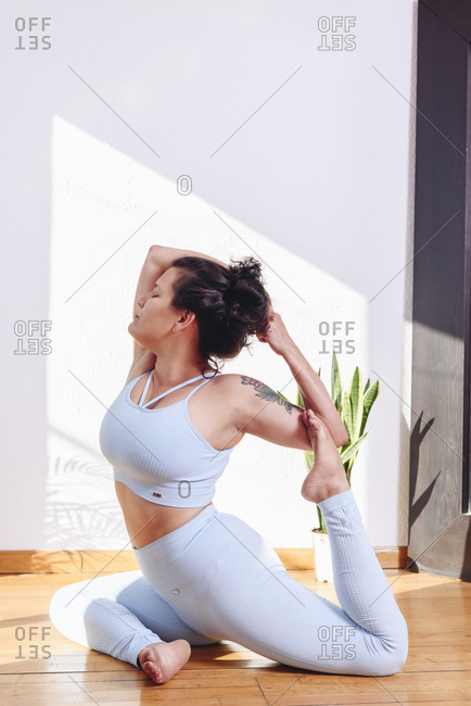 Side view of relaxed female in sportswear practicing yoga in Eka Pada Rajakapotasana while sitting on wooden floor at home with eyes closed