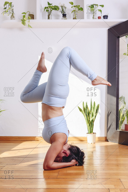 Side view of unrecognizable flexible female in sportswear balancing in handstand position while practicing yoga at home