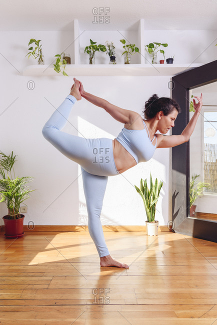 Side view of focused female in sportswear practicing yoga in Lord of the Dance Pose while standing on wooden floor at home
