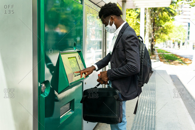 Side view of African American businessman in protective mask with suitcase using street ATM terminal in Barcelona city
