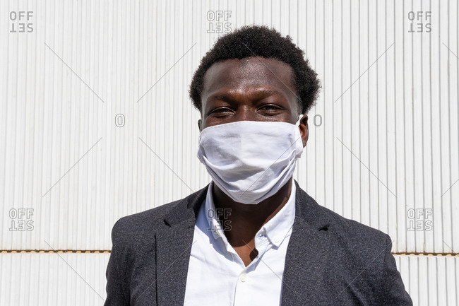 Positive young African American entrepreneur in formal wear and protective mask looking at camera while standing against wall on street
