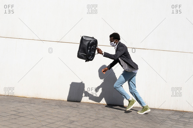 Side view of hurrying young African American businessman in protective mask carrying briefcase and running fast along wall on city street