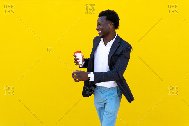 Cheerful African American male executive manager in formal wear standing with takeaway coffee in city during break and looking away on yellow background