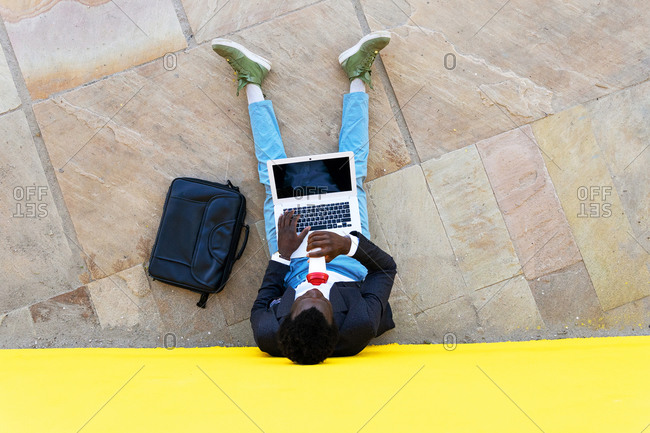 Top view of unrecognizable African American businessman in stylish clothes with briefcase drinking coffee and using laptop while sitting near wall on city street