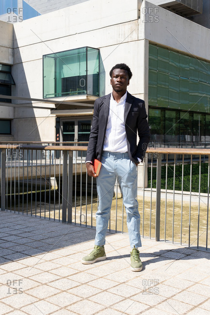 Full body of young African American male entrepreneur in elegant jacket and jeans holding organizer in hand and looking at camera while standing near contemporary urban building in Barcelona city