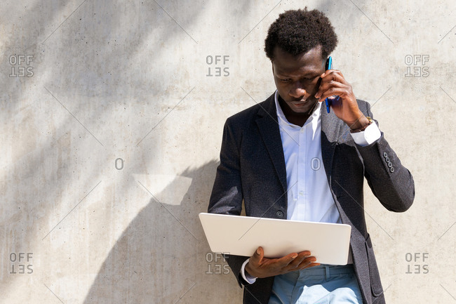 Focused African American male executive manager standing near building with laptop and discussing work issues on smartphone