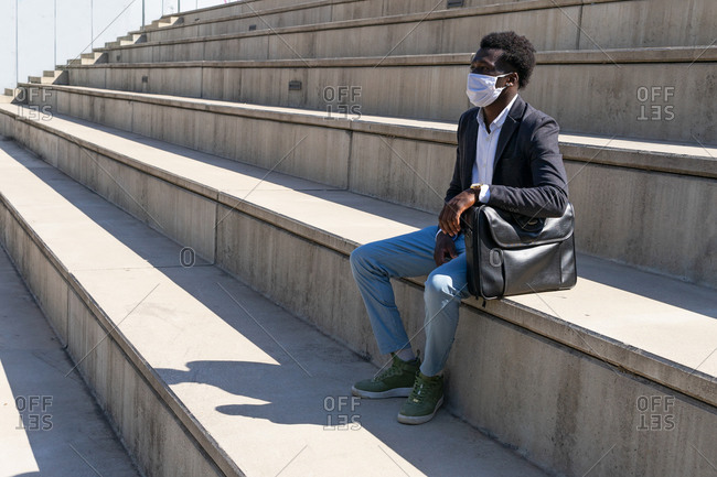 African American male entrepreneur wearing medical mask relaxing on stone stairs in city during coronavirus and looking away