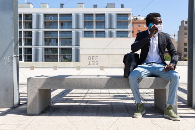 Black male entrepreneur wearing medical mask sitting on stone bench in city and discussing work issues on cellphone during COVID 19 epidemic