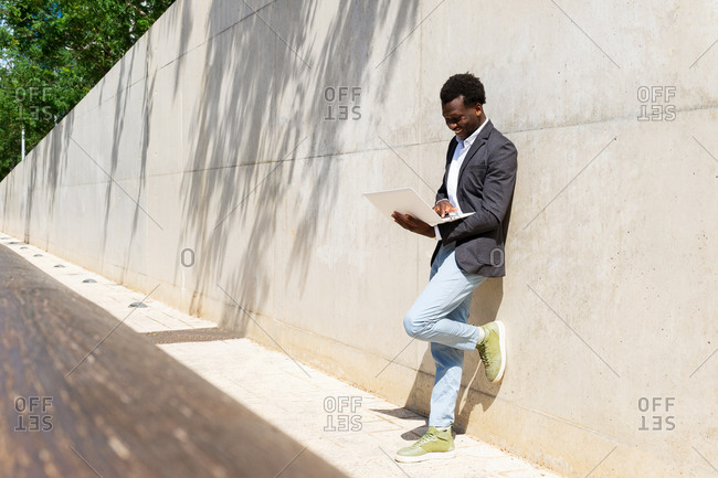 Focused African American male executive manager standing against concrete wall in the street with laptop