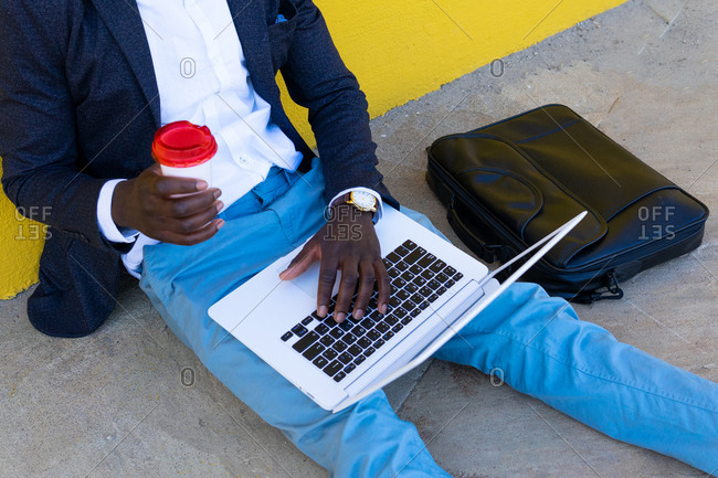 Cropped unrecognizable African American businessman in stylish clothes with briefcase drinking coffee and using laptop while sitting near wall on city street