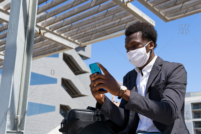 Low angle of busy African American male manager in protective mask sitting in city and browsing cellphone while working remotely on project during COVID 19 outbreak