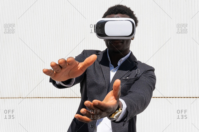 African American male standing experiencing virtual reality while using modern VR headset on yellow background in city