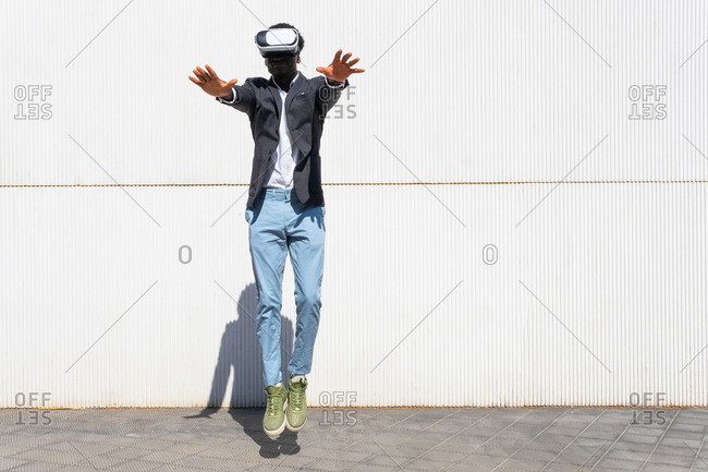 Carefree ethnic male wearing VR headset in moment of jumping and experiencing virtual reality