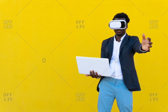 African American male entrepreneur standing with laptop and experiencing virtual reality while using modern VR headset on yellow background in city
