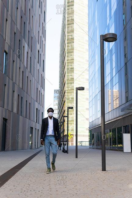 African American male entrepreneur in formal wear and medical mask walking along street during coronavirus epidemic