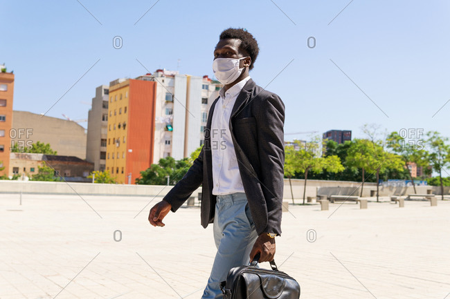 Well dressed black businessman in protective medical mask walking along street on sunny day in city during COVID 19 epidemic and looking away