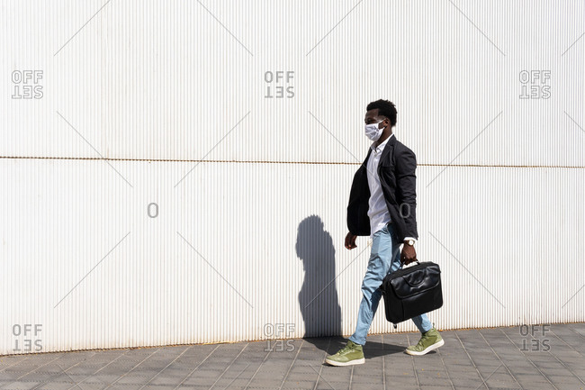 Side view of well dressed black male entrepreneur in medical mask walking along urban building on sunny day in city during coronavirus epidemic