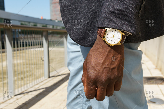 Side view of anonymous ethnic male entrepreneur wearing formal costume and elegant wristwatch standing in city on sunny day
